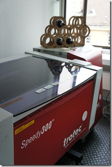 A laser cutter with a laser cut wine bottle holder