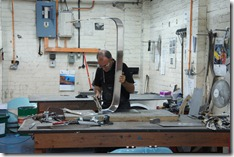 A specialist hand-shaping a metal panel