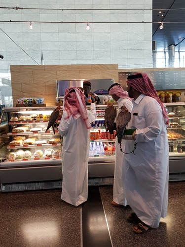 Men with falcons buying snacks