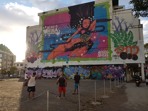 Locals playing petanque in front of another mural