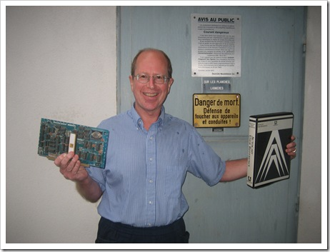 John Walker holding an M9900 and the prototype hardcover manual for AutoCAD 2.1